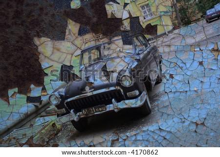 Aged vintage car on peeling paint background. - stock photo