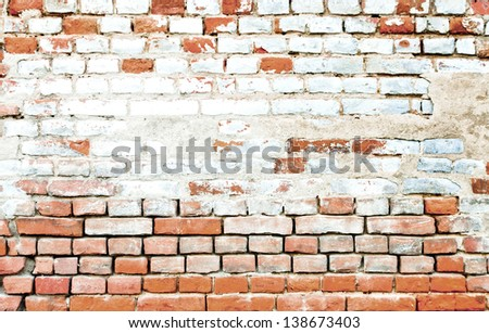 Aged wall of red and white bricks with the stain in the middle - stock photo