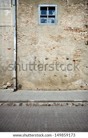 Aged weathered street wall with small window - stock photo