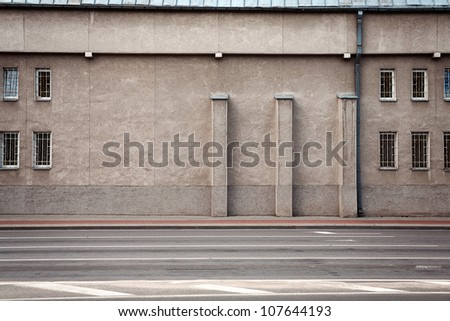 Aged weathered street wall with some windows - stock photo