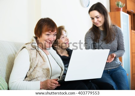 Aged women and happy girl with laptop in home interior - stock photo