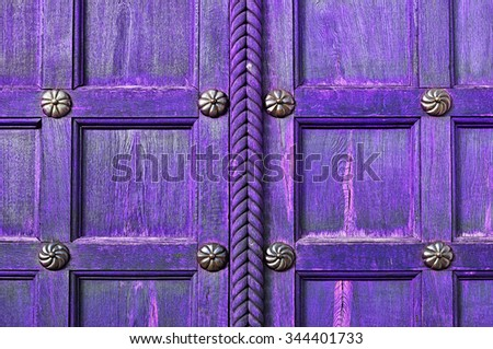 Aged wooden violet door  with metal bronze rivets on the  wooden textured surface - architectural textured background - stock photo