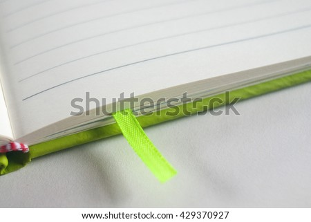 agenda - green bookmark - text space - paper background - stock photo
