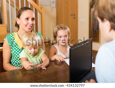 Agent consulting smiling mother with two kids how to obtain insurance - stock photo