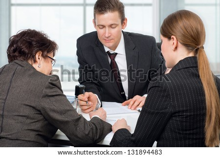Agent (or notary public) signing documents with couple women - stock photo