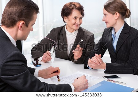 Agent (or notary public) signing documents with with senior woman and her daughter - stock photo
