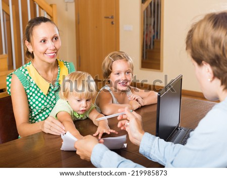 Agent talking with smiling mother and two little daughters about insurance at home. Focus on girl - stock photo