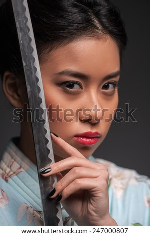 Aggressive beauty. Young beautiful Japanese woman in kimono looking at camera and holding katana sword by her face while standing against grey background - stock photo