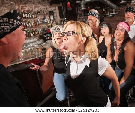 Aggressive female nerd sticking her tongue out at gang member - stock photo