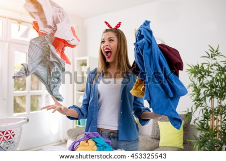Aggressive frustrated young woman throws laundry in the air - stock photo