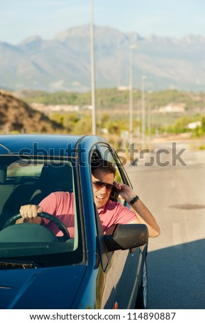 Aggressive guy yelling on the phone while driving - stock photo