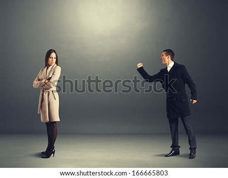 aggressive man yelling at the woman. photo in the dark room - stock photo