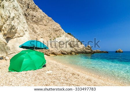 Agia Eleni beach in Kefalonia Island, Greece. One of the most beautiful rocky wild beaches of Kefalonia. Two green umbrellas on beautiful beach of Agia Eleni. - stock photo