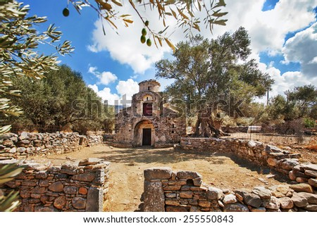 Agii Apostoli Byzantine with olives trees soft bokeh in foreground. This is a 10th-11th century Church in Naxos island, Greece. - stock photo