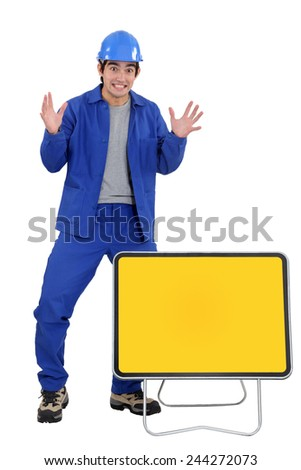 Agitated worker with a blank road sign - stock photo
