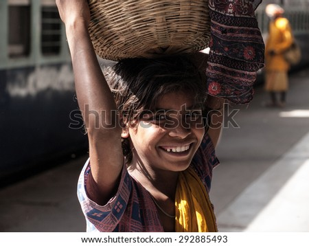 AGRA, INDIA-APRIL 17: Poor little girl is selling local cheap snack for train passenger in April 17, 2009 in Agra, India - stock photo