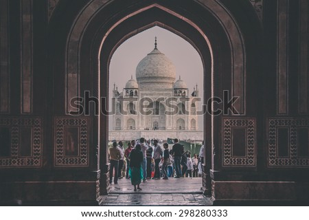 AGRA, INDIA - 28 FEBRUARY 2015: View of Taj Mahal from inside the Great Gate with visitors. Post-processed with grain, texture and colour effect. - stock photo