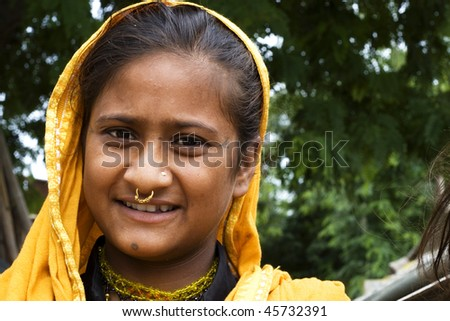 AGRA, INDIA - JUNE 19: Portrait of happy tribal woman in a village in india, from Agra June 19, 2008 in Agra, India. Local women wear colorful saree (sari) as traditional clothing. - stock photo