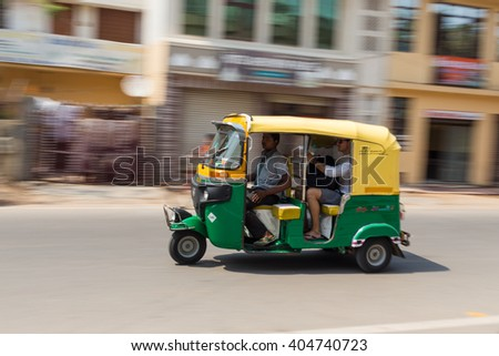 AGRA, INDIA - 26TH MARCH 2016: A Tuk Tuk Rickshaw moving along a road in Agra during the day. People can be seen. - stock photo