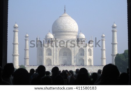 Agra, Uttar Pradesh, India - October 2011: The first view of the Taj Mahal, one of the New Seven Wonders of the World and visitors at the entrance of the complex. - stock photo