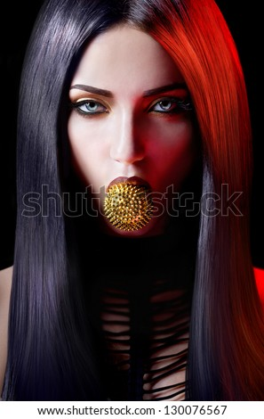 Agressive woman with a spiky toy in the mouth on a black background - stock photo