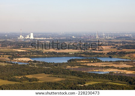 Agricultural and industrial landscape with a coal-fired power station, quarry pond and woods in the Lower Rhine Region of Germany - Aerial view of Rheinberg, North Rhine-Westfalia, Germany, Europe - stock photo