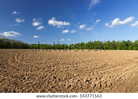 agricultural black field plowing under blue sky clouds. - stock photo