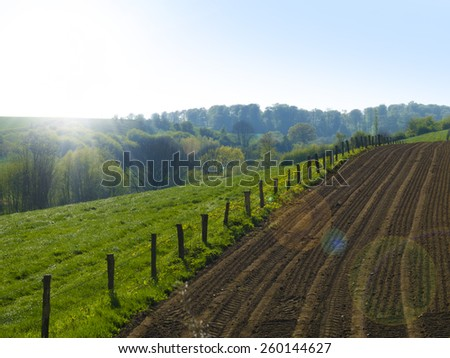 agricultural countryside landscape with freshly plowed field - stock photo