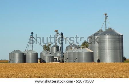 Agricultural grain bins in a farm field - stock photo