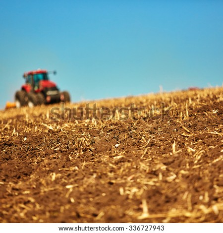 Agricultural Landscape. Tractor working on the field. Spring sunny day - stock photo