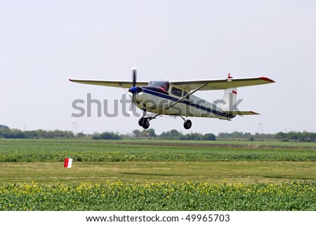 Agricultural plane is flying above green fields - stock photo
