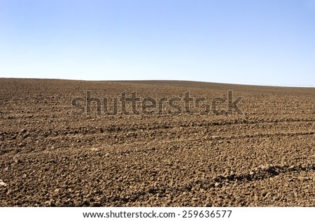 Agricultural plow soil and blue sky - stock photo