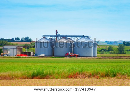 Agricultural silos in the fields, under blue sky - stock photo