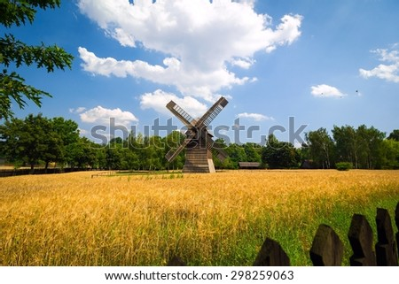 Agricultural summer landscape with old windmill and blue sky - stock photo