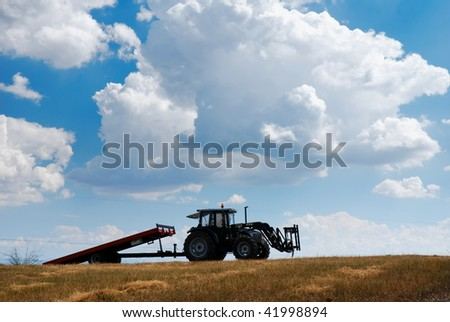 Agricultural tractor and trailer in dry field under cloudy blue sky - stock photo