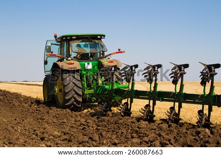 Agricultural tractor plowing a field before sowing - stock photo