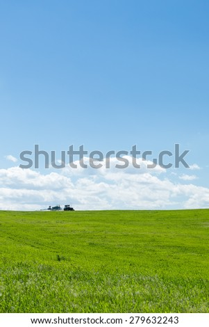 Agricultural tractor working in a green wheat field at noon - stock photo