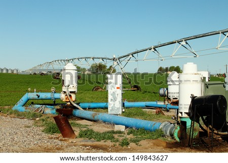 Agricultural water pumps and sprinklers watering a field of wheat - stock photo