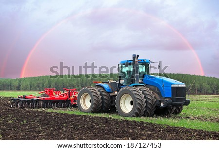 agricultural work plowing land on a powerful tractor - stock photo