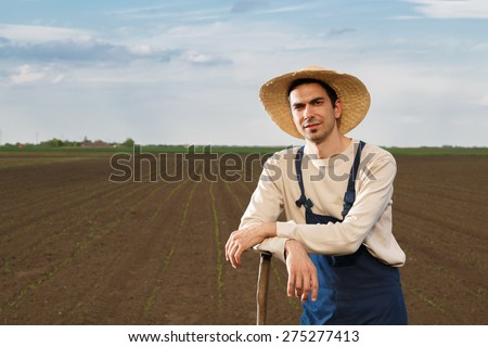 Agricultural worker posing on corn field with copy space - stock photo