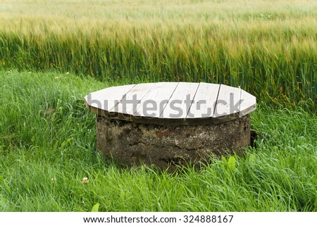 Agriculture drain well with cup in crop field - stock photo