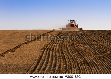 Agriculture tractor sowing seeds and cultivating field in late afternoon - stock photo