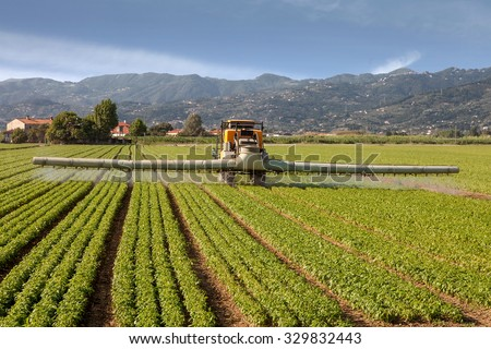 agriculture, tractor spraying pesticides on field farm - stock photo
