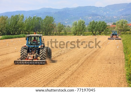 agriculture, two tractors working on a field - stock photo