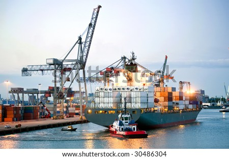 Ah huge container ship being maneuvered and reversed towards shore by pilots and tugboats - stock photo