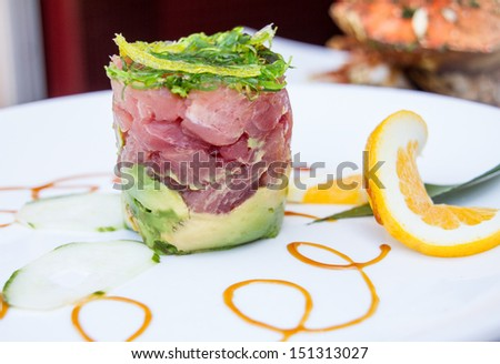 Ahi Tuna Tower appetizer with swirl design on the plate - stock photo
