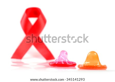 Aids ribbon and condom on white background.  - stock photo