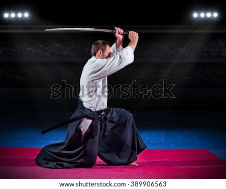 Aikido fighter with sword at sports hall - stock photo