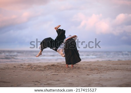 Aikido practitioners on the beach, throwing technique - stock photo
