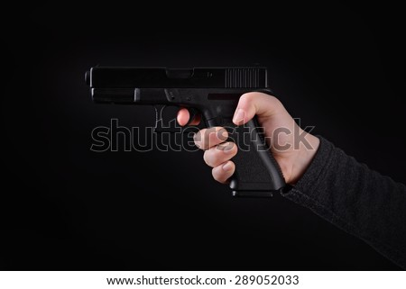 Aiming gun in female hand on a blsck background - stock photo